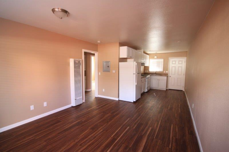 Wood Flooring. Living And Open Kitchen View. Wall Heater. Window Over The Kitchen Sink.