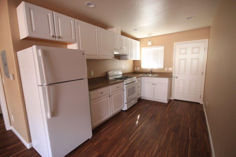Kitchen With Fridge, Stove And Cabinets. Same Wood Flooring In Living Room Kitchen And Hallway
