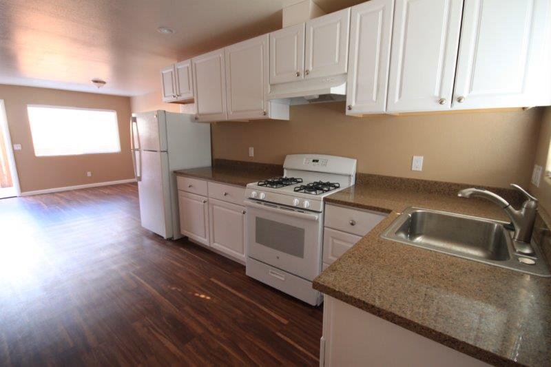 Kitchen Open To Living Room With Stainless Steel Sink, Gas Range. Wood Look Flooring Living Room And Kitchen
