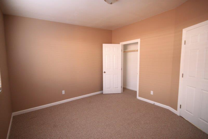 Bedroom With Berber Carpet Floor. Swing Open Closet Door With Closet Rod.