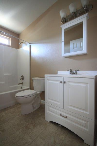 Bathroom With Vanity For Storage, A Mirror Medicine Cabinet, And Shower With Curtain Rod